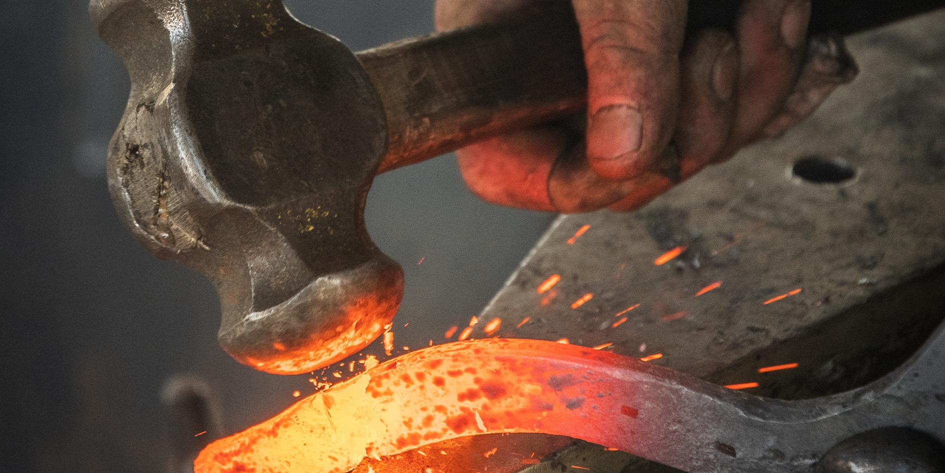 A Blacksmith hand hammering hot metal