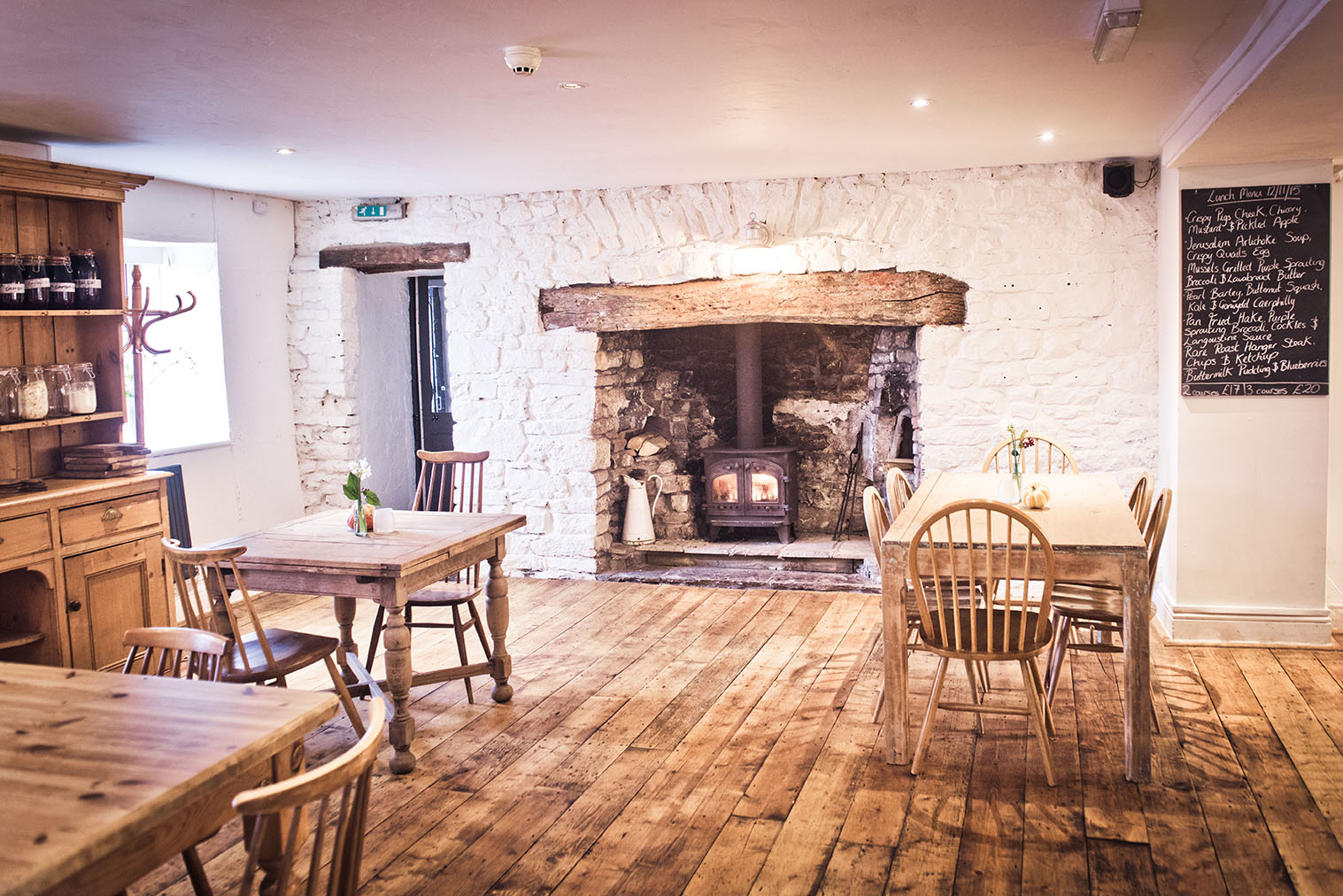 Hare and hounds dining room with wooden tables and chairs. Featuring a large fireplace
